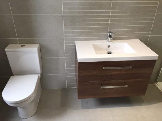mordern toilet and sink with dark wood drawers